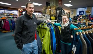 Sean Rielly and Courtney Nicholl, new owners of the Foggy Mountain Shop, pose for a picture at the North Franklin Street outdoors store in Juneau, Alaska, on Monday, Jan. 27, 2014. Both have been employees at the shop for years. (AP Photo/The Juneau Empire, Michael Penn)
