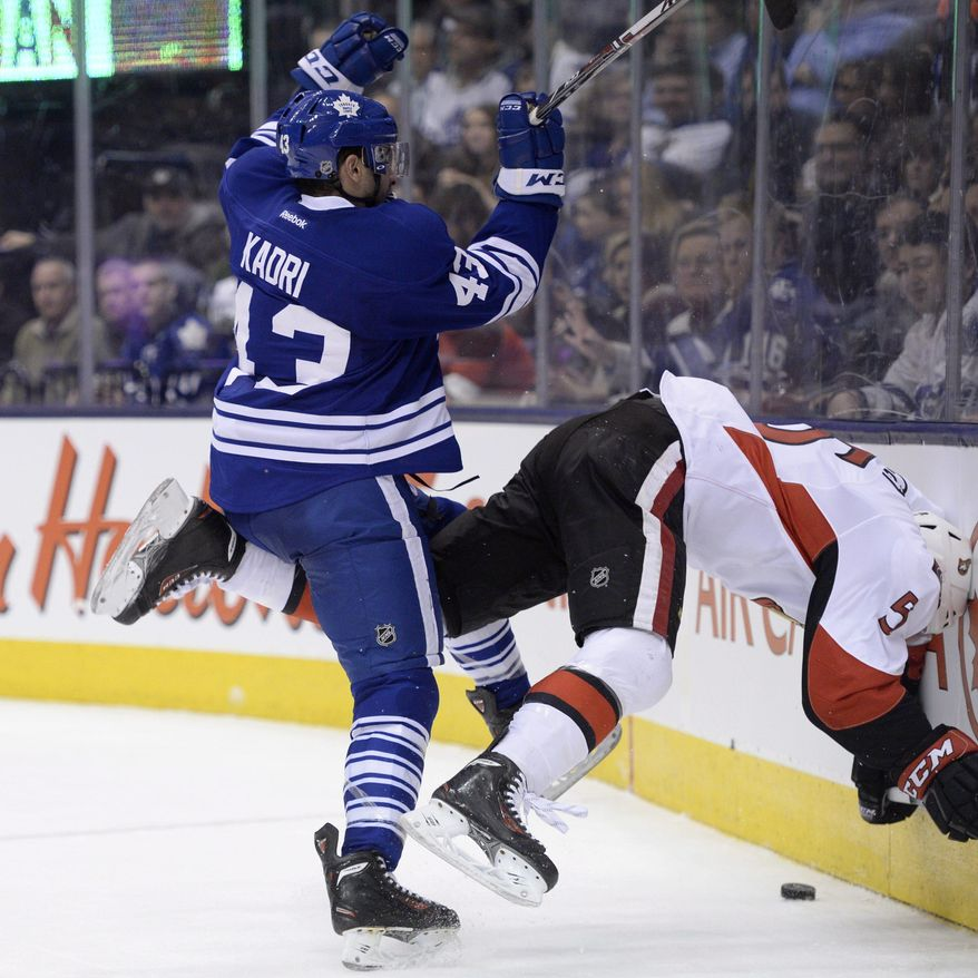 Toronto Maple Leafs' Nazem Kadri hits Ottawa Senators' Cody Ceci head first into the boards during second period of an NHL hockey game in Toronto, Saturday, Feb. 1, 2014. (AP Photo/The Canadian Press, Frank Gunn)