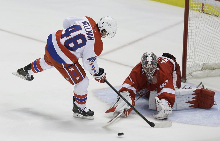 Detroit Red Wings goalie Jimmy Howard (35) deflects a shot by Washington Capitals center Casey Wellman (48) during the shootout of an NHL hockey game in Detroit, Friday, Jan. 31, 2014. The Red Wings won 4-3. (AP Photo/Carlos Osorio)