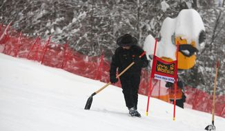A course worker clears fresh snow from the alpine ski, women's World Cup giant slalom course, in Kranjska Gora, Slovenia,  Saturday, Feb. 1, 2014. The final women's World Cup giant slalom before the Sochi Olympics has been called off because of bad weather, following a day of heavy snowfall.  FIS says 200 course workers have been working all morning to clear over a meter of fresh snow, but rain and fog are limiting visibility for the racers on the softened course. ( AP Photo/Giovanni Auletta)