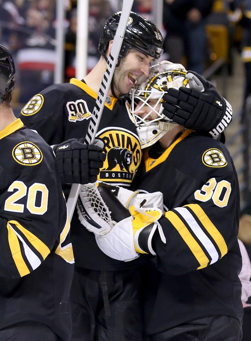 Boston Bruins defenseman Zdeno Chara, of Slovakia, congratulates goalie Chad Johnson after the 4-0 win over the Edmonton Oilers during the third period of an NHL hockey game, Saturday, Feb. 1, 2014 in Boston. (AP Photo/Mary Schwalm)