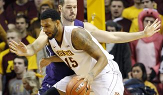 Minnesota forward Maurice Walker (15) drives against Northwestern forward Nikola Cerina during the first half of an NCAA college basketball game in Minneapolis, Saturday, Feb. 1, 2014. (AP Photo/Ann Heisenfelt)