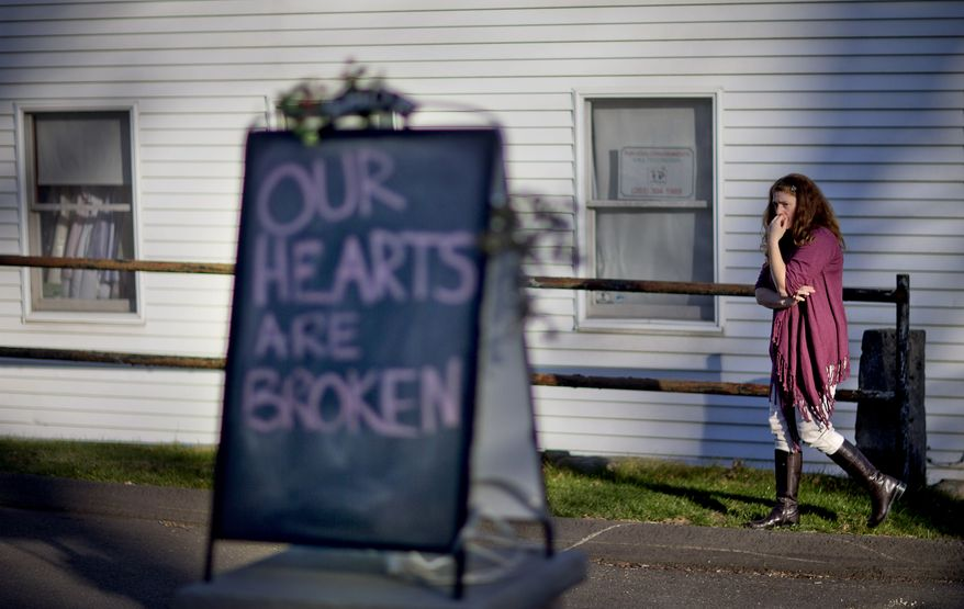 ** FILE ** In this Dec. 15, 2012, file photo, shop owner Tamara Doherty paces outside her store just down the road from Sandy Hook Elementary School in Newtown, Conn. (AP Photo/David Goldman, File)