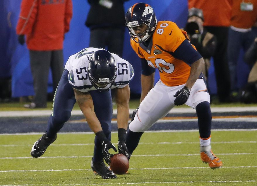 Seattle Seahawks' Malcolm Smith (53) recovers a fumble by Denver Broncos' Demaryius Thomas as Broncos' Julius Thomas (80) watches during the second half of the NFL Super Bowl XLVIII football game Sunday, Feb. 2, 2014, in East Rutherford, N.J. (AP Photo/Matt York)