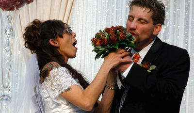 In this Feb. 1, 2014 photo, Craig Rouch takes a bite out of his bride April's bacon bouquet before their wedding during the Blue Ribbon Bacon Festival at the Iowa State Fairgrounds in Des Moines, Iowa. (AP Photo/The Des Moines Register, Zach Boyden-Holmes) MAGS OUT, TV OUT, NO SALES, MANDATORY CREDIT