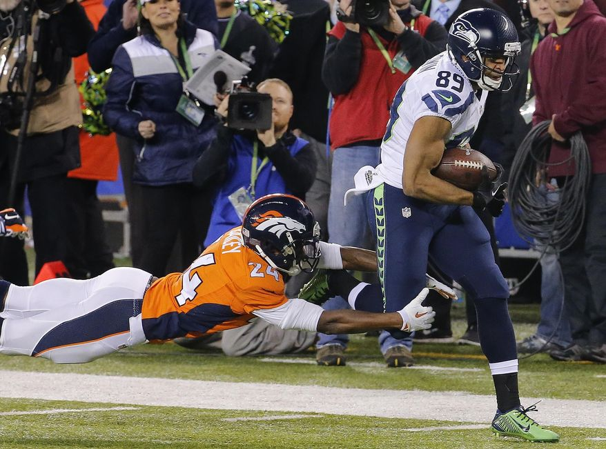 Denver Broncos cornerback Champ Bailey (24) reaches for Seattle Seahawks wide receiver Doug Baldwin (89) during the first half of the NFL Super Bowl XLVIII football game Sunday, Feb. 2, 2014, in East Rutherford, N.J. (AP Photo/Matt York)