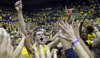 California's David Kravish, center, celebrates with fans on the court after a last-second win over Arizona during the second half on an NCAA college basketball game on Saturday, Feb. 1, 2014, in Berkeley, Calif. California won 60-58. (AP Photo/Marcio Jose Sanchez)
