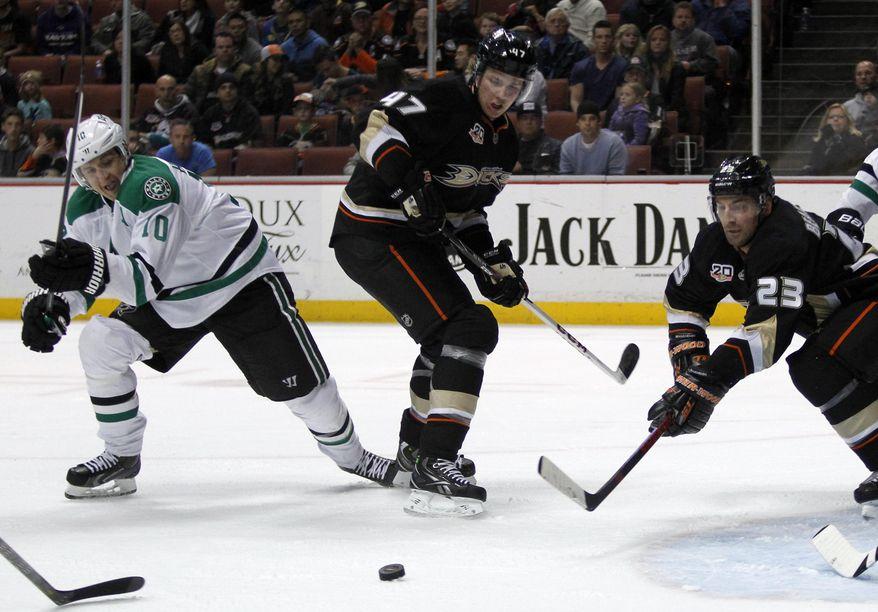 Dallas Stars center Shawn Horcoff (10) battles Anaheim Ducks defenseman Hampus Lindholm (47), of Sweden and defenseman Francois Beauchemin (23) for the puck in the first period of an NHL hockey game Saturday, Feb. 1, 2014, in Anaheim, Calif. (AP Photo/Alex Gallardo)
