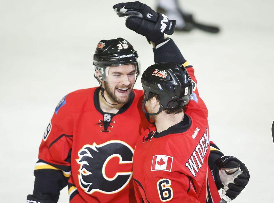 Calgary Flames' Dennis Wideman, right, celebrates his goal with teammate TJ Galiardi during second period of an NHL hockey game in Calgary, Alberta, Saturday, Feb. 1, 2014. (AP Photo/The Canadian Press, Jeff McIntosh)