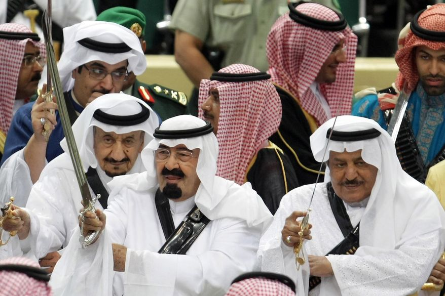 FILE - In this Tuesday, March 23, 2010 file photo, King Abdullah, center, of Saudi Arabia and his half brother Saudi Interior Minister Prince Nayef bin Abdul Aziz al-Saud, right, hold their swords as they take part in the traditional Arda dance, or War dance, during the Janadriyah Festival of Heritage and Culture on the outskirts of Riyadh, Saudi Arabia. King Abdullah has ratified a new counter-terrorism law which went into effect Sunday, Feb. 2, 2014. Rights activists said that the law criminalizes speech critical of the government or society. It was published in full in the government's official gazette Um Al-Qura Friday. (AP Photo, File)