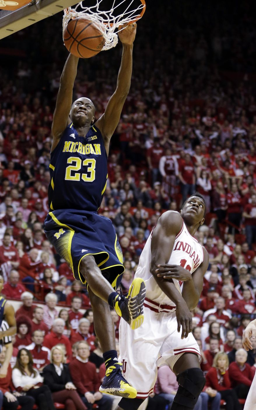 Michigan guard Caris LeVert (23) dunks over Indiana forward Hanner Mosquera-Perea in the first half of an NCAA college basketball game in Bloomington, Ind., Sunday, Feb. 2, 2014. (AP Photo/Michael Conroy)