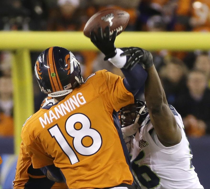 Denver Broncos' Peyton Manning is hit by Seattle Seahawks' Cliff Avril as he throws an interception during the first half of the NFL Super Bowl XLVIII football game Sunday, Feb. 2, 2014, in East Rutherford, N.J. (AP Photo/Mark Humphrey)