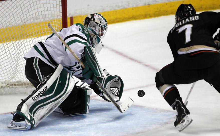 Dallas Stars goalie Dan Ellis, left, stops a shot by Anaheim Ducks center Andrew Cogliano in the second period of an NHL hockey game Saturday, Feb. 1, 2014, in Anaheim, Calif. (AP Photo/Alex Gallardo)