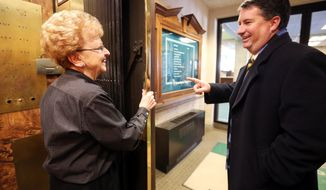 EXCHANGE FOR RELEASE SUNDAY, FEB. 2, 2014, AT 12:01 A.M. CST AND THEREAFTER  - In this Jan. 27, 2014 photo, Ann Kearney, left, jokes around with Gary McAndrew at American Trust and Savings Bank in Dubuque, Iowa. Kearney, who operates the elevator, will retire after 32 years with the company. (AP Photo/The Telegraph Herald, Jessica Reilly)