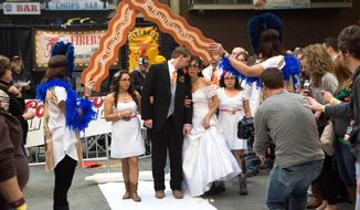 In this Feb. 1, 2014 photo, Craig Roush and April DaVila get ready to walk down the aisle for their wedding during the Blue Ribbon Bacon Festival at the Iowa State Fairgrounds in Des Moines, Iowa. (AP Photo/The Des Moines Register, Scott Morgan) MAGS OUT, TV OUT, NO SALES, MANDATORY CREDIT