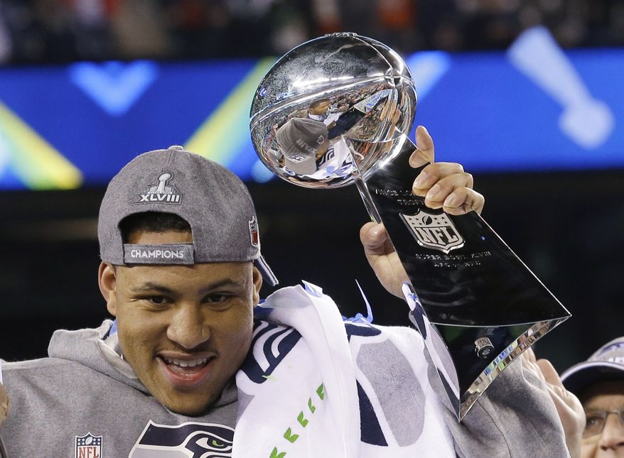 Seattle Seahawks' Malcolm Smith celebrates with the Vince Lombardi Trophy after the NFL Super Bowl XLVIII football game against the Denver Broncos Sunday, Feb. 2, 2014, in East Rutherford, N.J. The Seahawks won 43-8. (AP Photo/Ted S. Warren)