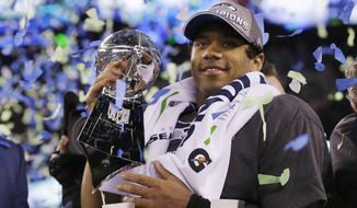 Seattle Seahawks' quarterback Russell Wilson holds the Lombardi Trophy after the NFL Super Bowl XLVIII football game Sunday, Feb. 2, 2014, in East Rutherford, N.J. The Seahawks won 43-8. (AP Photo/Julio Cortez)