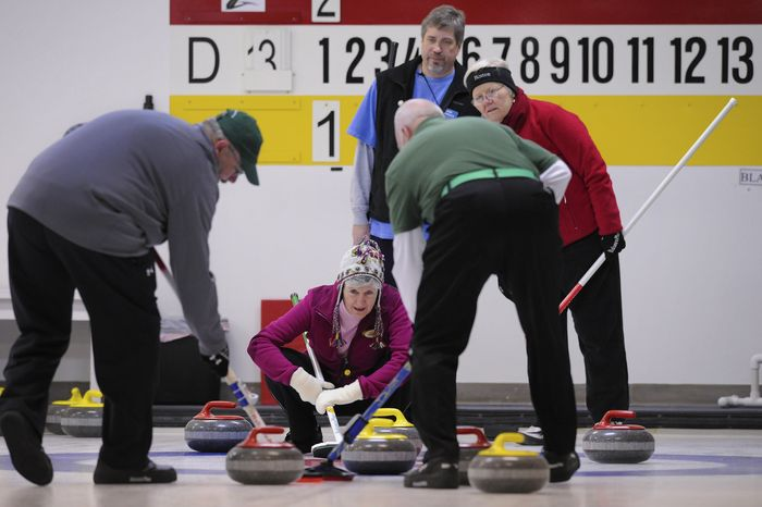 Jeanne Kenkel  (center), from the Chesapeake Curling Club, Md., provides the the sweepers direction during the curling competition at the Potomac Curling Club in Laurel, Md.