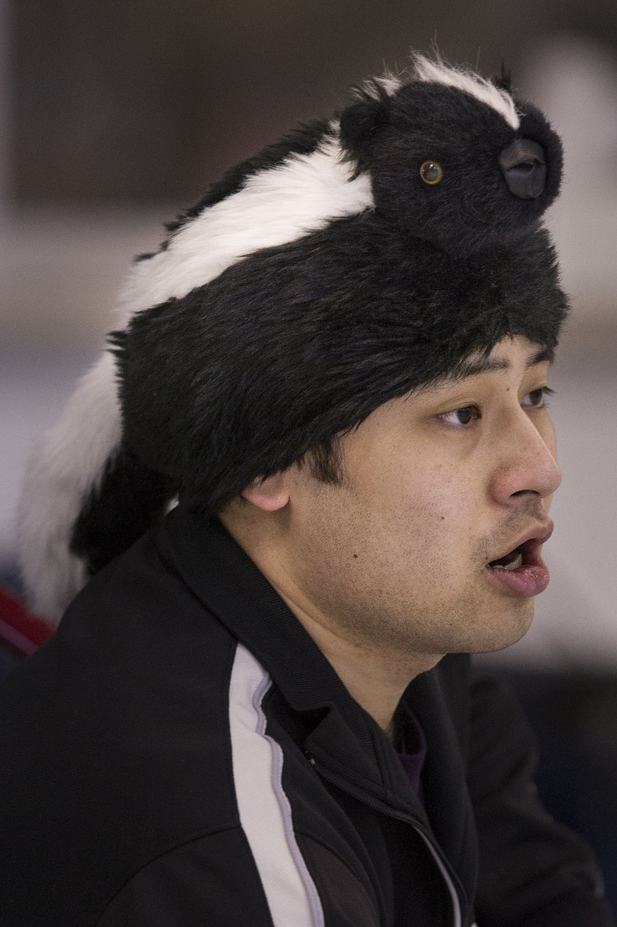 Sporting his skunk hat, Eugene Huang from the Plainfield Curling Club, N.J., barks directions  during the curling competition at the Potomac Curling Club in Laurel, Md. (Preston Keres/Special to The Washington Times)
