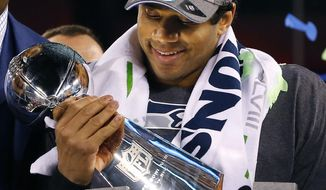 Seattle Seahawks quarterback Russell Wilson holds the Lombardi Trophy after the NFL Super Bowl XLVIII football game Sunday, Feb. 2, 2014, in East Rutherford, N.J. The Seahawks won 43-8. (AP Photo/Paul Sancya)