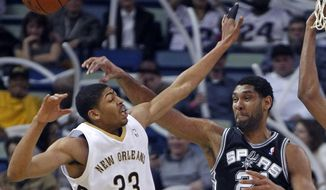 New Orleans Pelicans forward Anthony Davis (23) and San Antonio Spurs forward Tim Duncan (21) battle for a loose ball in the first half of an NBA basketball game in New Orleans, Monday, Feb. 3, 2014. (AP Photo/Gerald Herbert)
