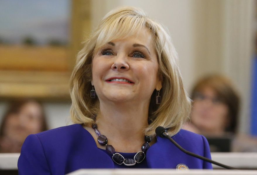 Oklahoma Governor Mary Fallin smiles as she introduces her family at the start of her State of the State address in Oklahoma City, Monday, Feb. 3, 2014. Fallin renewed her call for a cut in the state's income tax rate and asked legislators to approve a bond issue to help repair the state Capitol Monday during her fourth State of the State speech. (AP Photo/Sue Ogrocki)