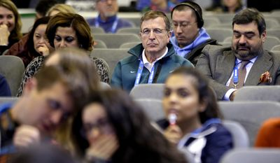 International Olympic Committee Executive Director Gilbert Felli, center, listens during a press conference with IOC President Thomas Bach at the 2014 Winter Olympics, Monday, Feb. 3, 2014, in Sochi, Russia. (AP Photo/David Goldman)