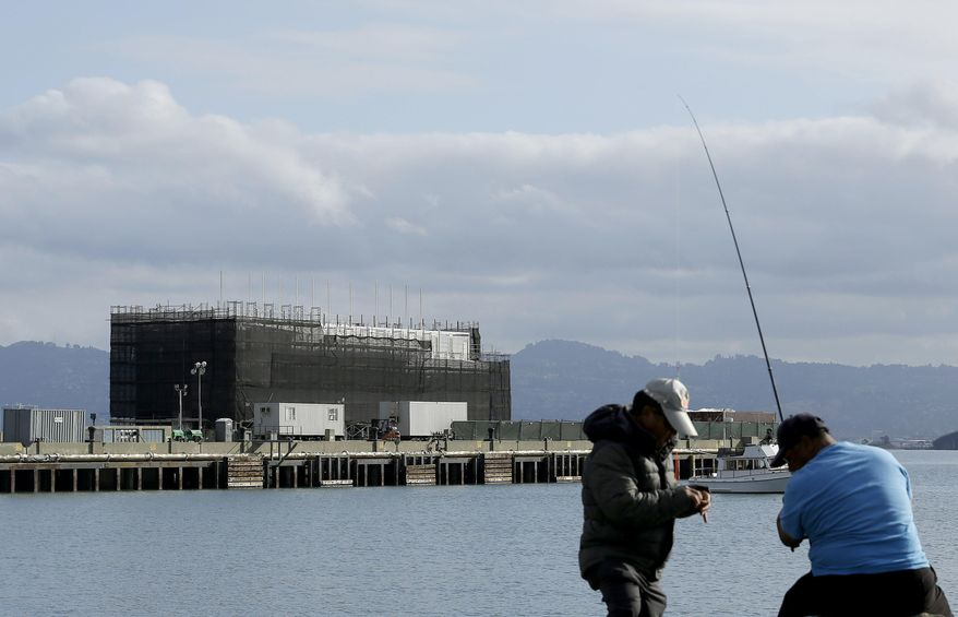 FILE - In this Tuesday, Oct. 29, 2013, file photo, two men fish in the water in front of a Google barge on Treasure Island in San Francisco. A state agency says Google must move its mystery barge from a construction site on an island in the middle of the San Francisco Bay because the permits are not in order. (AP Photo/Jeff Chiu, File)