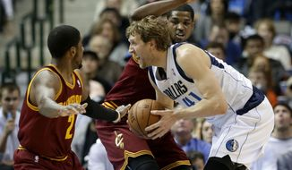 Dallas Mavericks power forward Dirk Nowitzki (41) of Germany drives between Cleveland Cavaliers' Kyrie Irving (2) and Tristan Thompson, rear, to the basket for a shot attempt in the first half of an NBA basketball game, Monday, Feb. 3, 2014, in Dallas. (AP Photo/Tony Gutierrez)