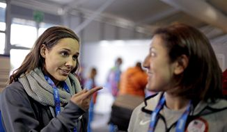United States bobsled brakeman Lolo Jones, left, gestures to teammate, pilot Elana Meyers, during a television interview as the pair arrive at the 2014 Winter Olympics, Thursday, Jan. 30, 2014, in Sochi, Russia. (AP Photo/David Goldman, Pool)