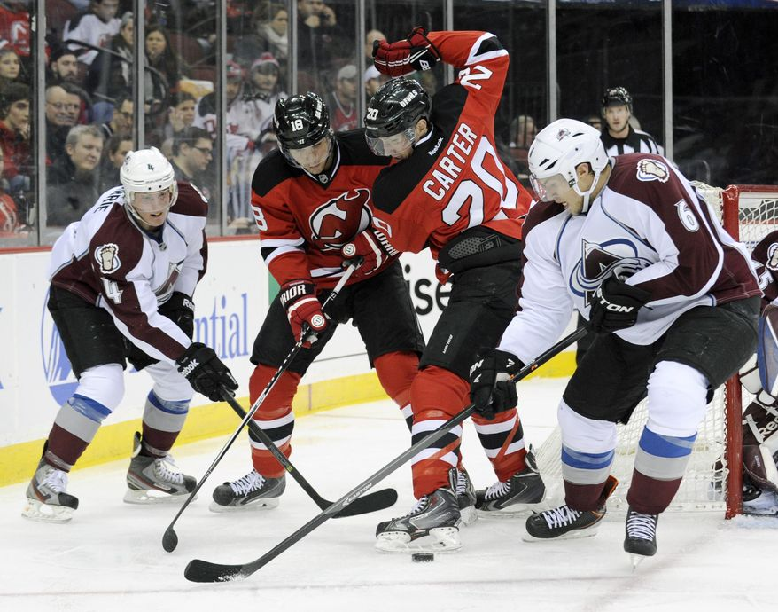 Colorado Avalanche's Erik Johnson, right, and Tyson Barrie, left, battle for control of the puck against New Jersey Devils' Ryan Carter (20) and Steve Bernier during the second period of an NHL hockey game, Monday, Feb. 3, 2014, in Newark, N.J. (AP Photo/Bill Kostroun)