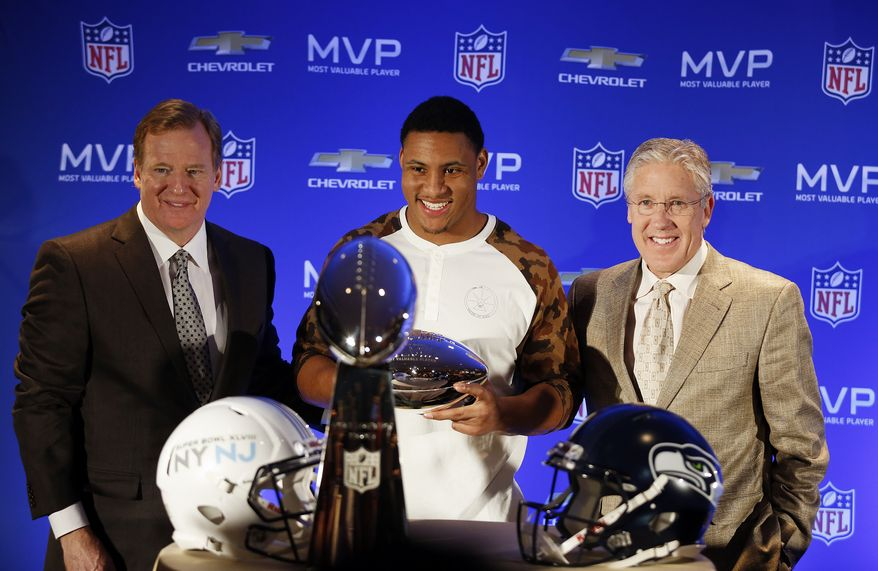 Left to right, NFL Commissioner Roger Goodell, Seattle Seahawks linebacker Malcolm Smith, and Seahawks head coach Pete Carroll pose for photos during the Super Bowl Most Valuable Player and winning coach press conference, Monday, Feb. 3, 2014, in New York. (AP Photo/Doug Benc)