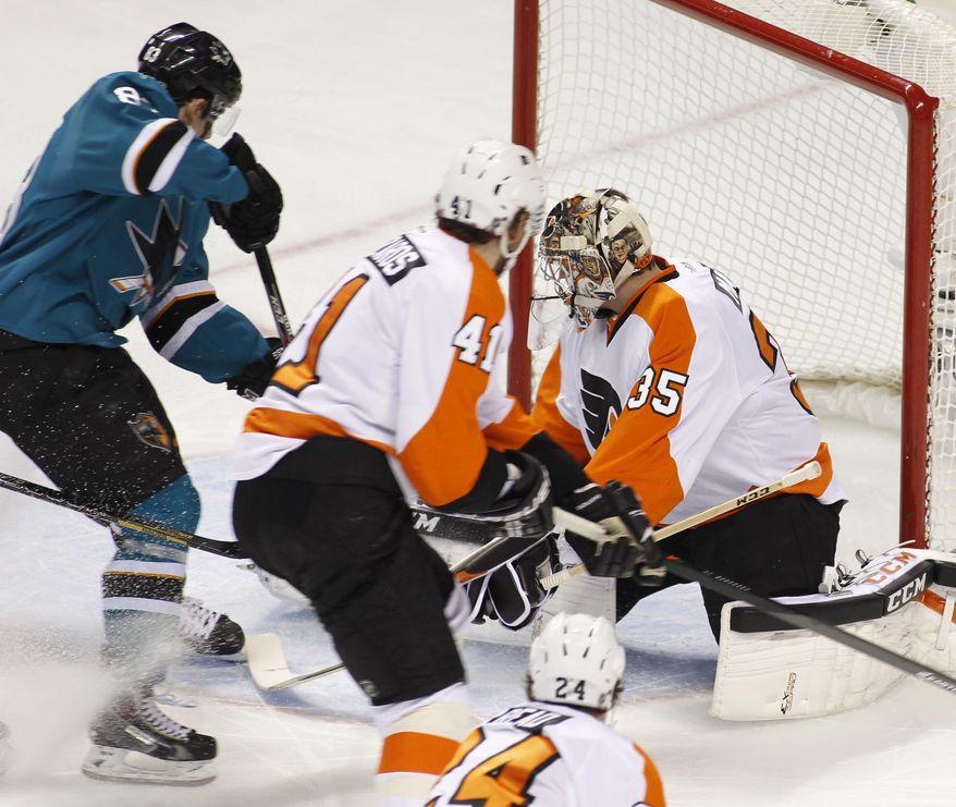 San Jose Sharks' Matt Nieto, left, scores past Philadelphia Flyers goalie Steve Mason (35) during the first period of an NHL hockey game, Monday, Feb. 3, 2014, in San Jose, Calif. (AP Photo/George Nikitin)