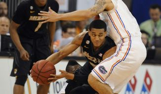 Missouri guard Jordan Clarkson tries to get past Florida guard Scottie Wilbekin, right, during the first half of an NCAA college basketball game Tuesday, Feb. 4, 2014, in Gainesville, Fla. (AP Photo/Phil Sandlin)