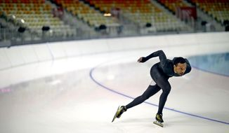 United States long track speed skater Shani Davis glides around a turn as he practices in Adler Arena for the 2014 Winter Olympics, Friday, Jan. 31, 2014, in Sochi, Russia. (AP Photo/David Goldman)