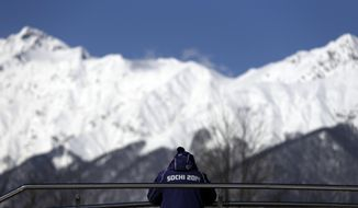 A member of the security team watches over the sliding center during women's luge training at the 2014 Winter Olympics, Tuesday, Feb. 4, 2014, in Krasnaya Polyana, Russia. (AP Photo/Natacha Pisarenko)