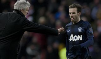 Manchester United's Juan Mata, right, walks past the opposing team's manager Mark Hughes after his team's 2-1 loss at Stoke in their English Premier League soccer match at the Britannia Stadium, Stoke, England, Saturday Feb. 1, 2014. (AP Photo/Jon Super)