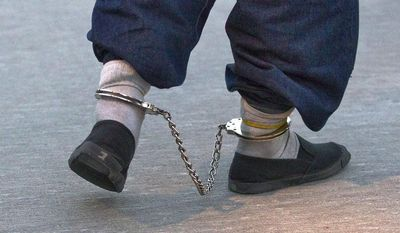 ** FILE ** In this June 26, 2012, file photo, a shackled illegal immigrant from El Salvador walks to an aircraft for a repatriation flight back to El Salvador from Phoenix-Mesa Gateway Airport in Mesa, Ariz. (AP Photo/Matt York,File)