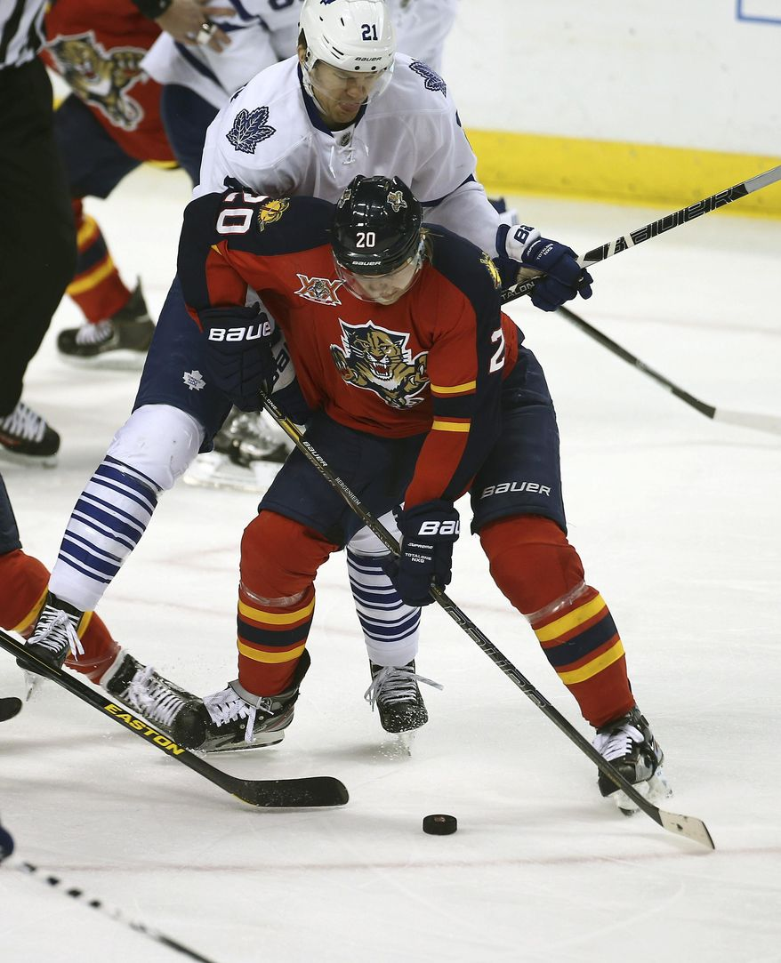 Toronto Maple Leafs' James van Riemsdyk (21) applies pressure as Florida Panthers' Sean Bergenheim (20) looks for a shot during the first period of an NHL hockey game in Sunrise, Fla., Tuesday, Feb. 4, 2014. (AP Photo/J Pat Carter)