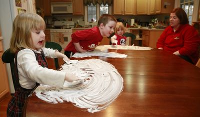 Joanne Kehoe, right, watches while her children, from left,  Maria, Anthony and Veronica play with shaving cream on the kitchen table while trying to combat cabin fever, Monday, Feb. 3, 2014, in Indianapolis. (AP Photo/R Brent Smith)