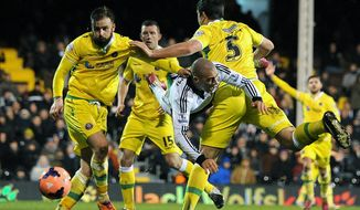 Fulham's Pajtim Kasami, centre,  goes down in the penalty area under a challenge from Sheffield United's Harry Maguire, right, during their 4th round replay English FA Cup soccer match between Fulham and Sheffield United at Craven Cottage stadium in London, Tuesday, Feb. 4, 2014.  (AP Photo / Andrew Matthews, PA) UNITED KINGDOM OUT - NO SALES - NO ARCHIVES