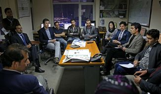 In this Monday, Feb. 3, 2014 photo, Tolo TV staffers talk during a meeting at their office in Kabul, Afghanistan. The proliferation of Afghan media in the past 12 years is one of the most visible bright spots of the fraught project to foster a stable democracy. (AP Photo/Massoud Hossaini)