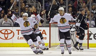 Chicago Blackhawks' Ben Smith (28), left, and defenseman Michael Kostka (6) celebrate a goal by Marcus Kruger, not shown, against Los Angeles Kings goalie Jonathan Quick (32) and defenseman Matt Greene (2) look on in the second period of an NHL hockey game in Los Angeles, Monday, Feb. 3, 2014. (AP Photo/Reed Saxon)