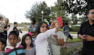 In this Jan. 10, 2014 photo, Katalina Valley, 11, tries to get a picture of a black bear in a tree in Apopka, Fla. (AP Photo/The Tampa Bay Times, Melissa Lyttle)