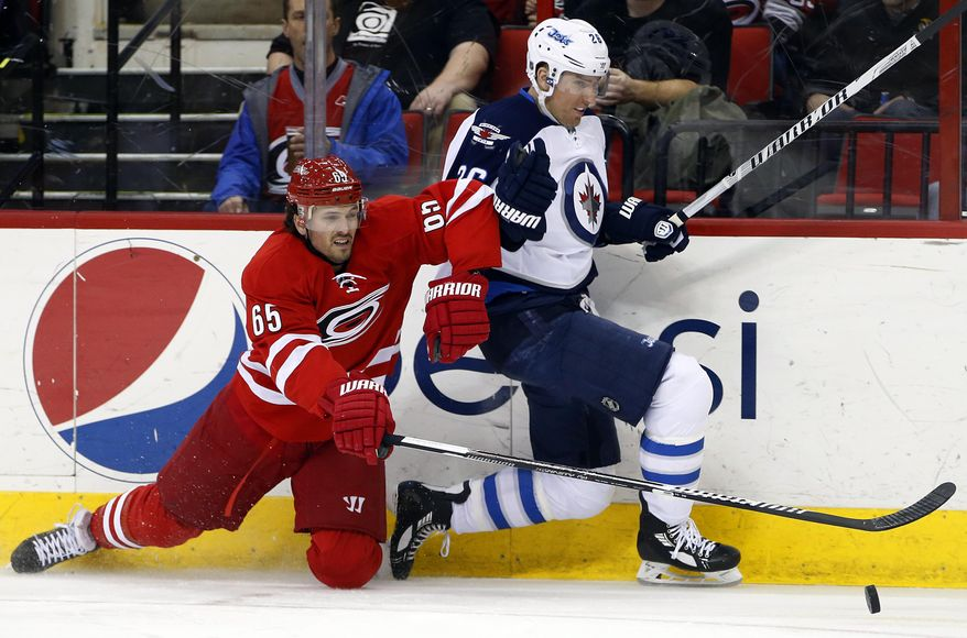 Winnipeg Jets' Blake Wheeler (26) and Carolina Hurricanes' Ron Hainsey (65) collide along the boards during the first period of an NHL hockey game in Raleigh, N.C., Tuesday, Feb. 4, 2014. (AP Photo/Karl B DeBlaker)
