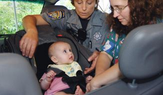 FILE - In this Sept. 20, 2005 file photo, South Windsor Police Department Community Service Officer Robin Massanti helps Debra Mlinek from West Suffield secure her daughter, Eliza, five months, in her car seat during a Child Passenger Safety Clinic in Hartford, Conn. In a report covering 2002 through 2011, Centers for Disease Control and Prevention officials say the increased use of car seats and booster seats drove a decline in children who died in crashes. (AP Photo/Fred Beckham)