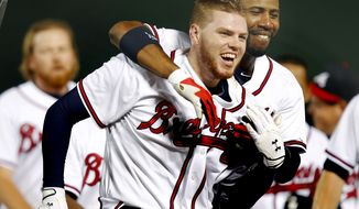 Atlanta Braves first baseman Freddie Freeman, left,  gets hugged by teammate Jason Heyward, after driving in the winning run with a two-run base hit in the ninth inning of a baseball game  against the San Francisco Giants Monday, Aug. 15,  2011 in Atlanta.  Atlanta won 5-4. (AP Photo/John Bazemore)