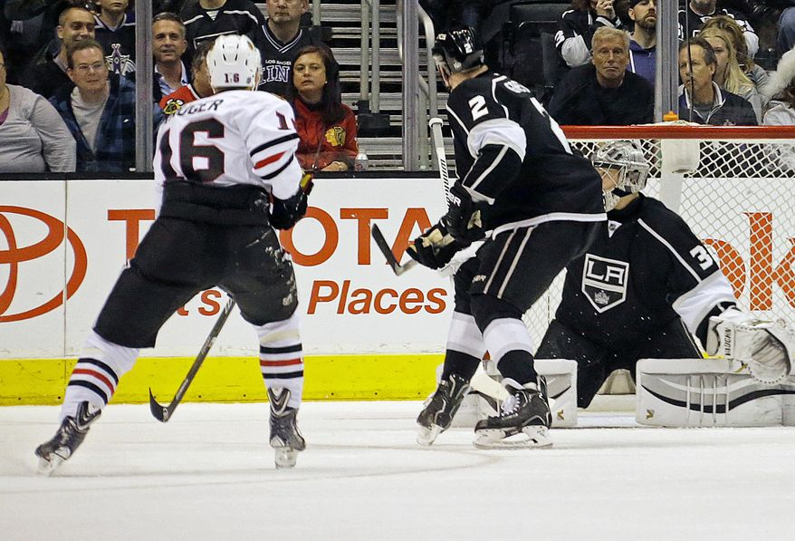 Chicago Blackhawks center Marcus Kruger (16) scores a goal against Los Angeles Kings goalie Jonathan Quick (32) and defenseman Matt Greene (2) in the second period of an NHL hockey game in Los Angeles, Monday, Feb. 3, 2014. (AP Photo/Reed Saxon)