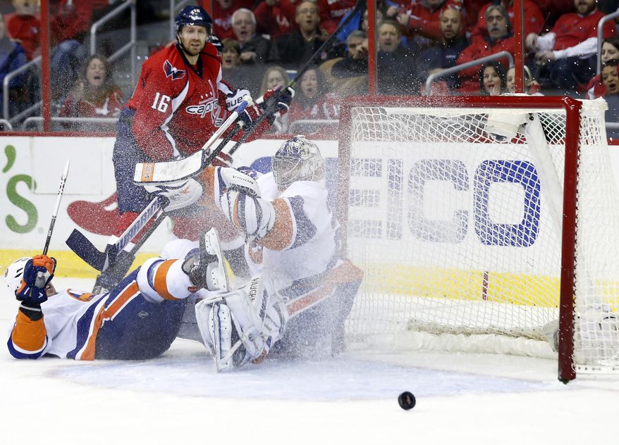 New York Islanders goalie Evgeni Nabokov (20), from Russia, watches the shot by Washington Capitals right wing Eric Fehr (16) bounce away, in the first period of an NHL hockey game, Tuesday, Feb. 4, 2014, in Washington. (AP Photo/Alex Brandon)