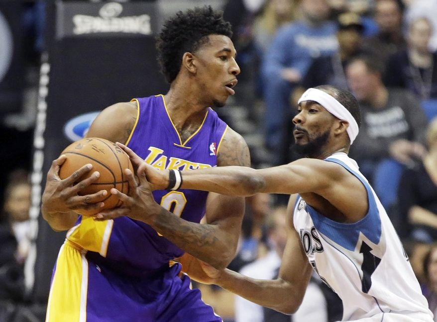 Minnesota Timberwolves' Corey Brewer, right, tries to knock the ball away from Los Angeles Lakers' Nick Young during the first quarter of an NBA basketball game, Tuesday, Feb. 4, 2014, in Minneapolis. (AP Photo/Jim Mone)
